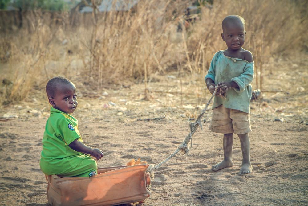 Kaksi nigerialaista lasta leikkii pihalla